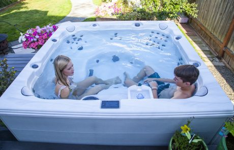 Boy and girl sitting in a hot tub